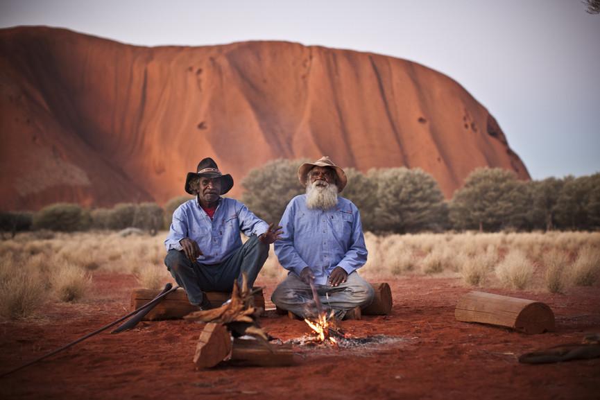 Aborigènes devant le site sacré Uluru