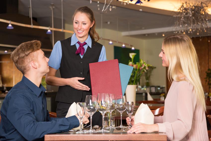 serveuse dans un restaurant présente le menu